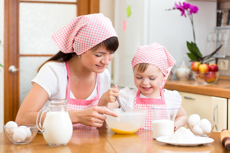 Mother and daughter cooking together at kitchen royalty free stock photos