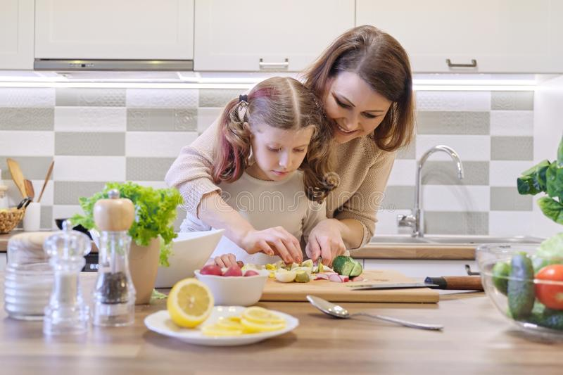 Mother and daughter cooking together in kitchen vegetable salad, parent and child are talking smiling stock photography