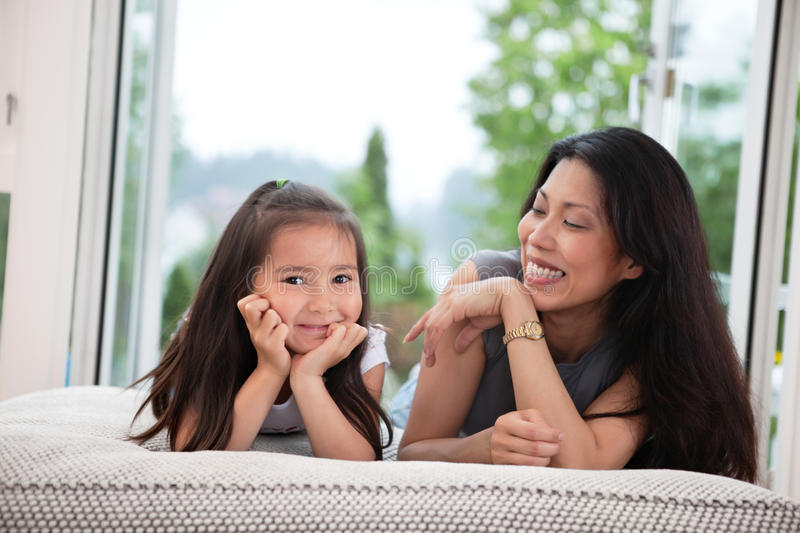 Mother and daughter on couch laughing stock photos