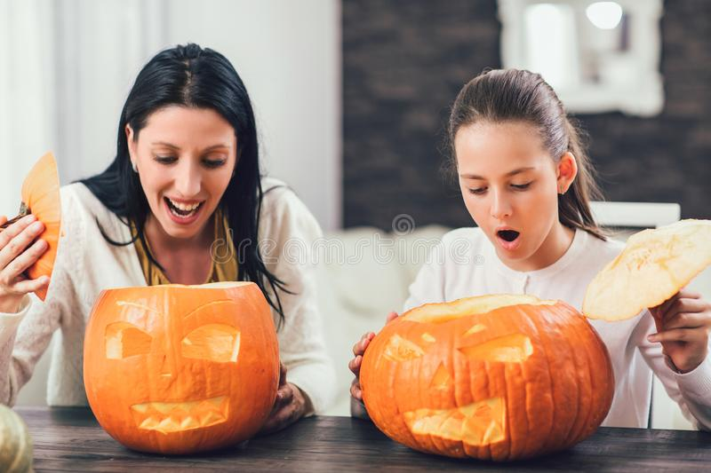 Mother with daughter creating big orange pumpkin for Halloween stock photos