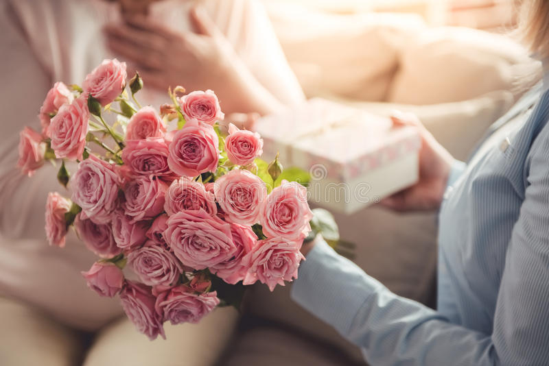 Mother and daughter. Cropped image of beautiful adult women giving flowers and a gift box to her mature mother royalty free stock photo