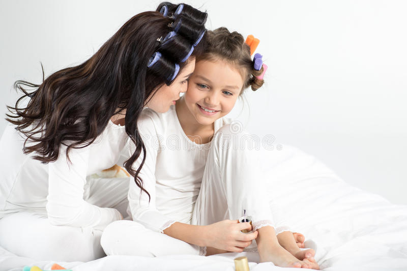 Mother and daughter in curlers and pajamas sitting together on bed. Happy mother and daughter in curlers and pajamas sitting together on bed stock photography