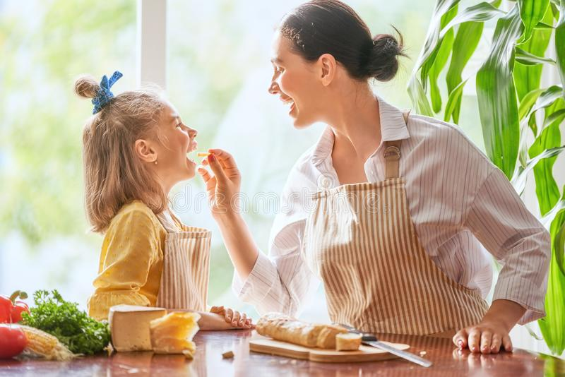 Mother and daughter cutting bread and cheese royalty free stock images