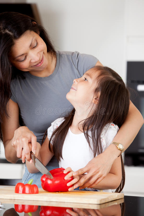 Mother and Daughter Cutting Vegetables stock image