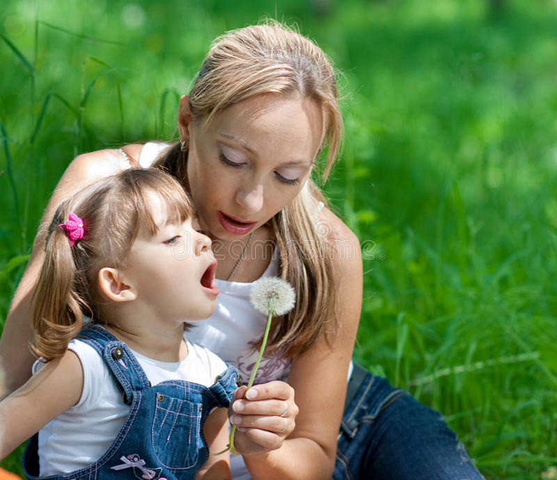 Mother and daughter with dandelion summertime royalty free stock photo