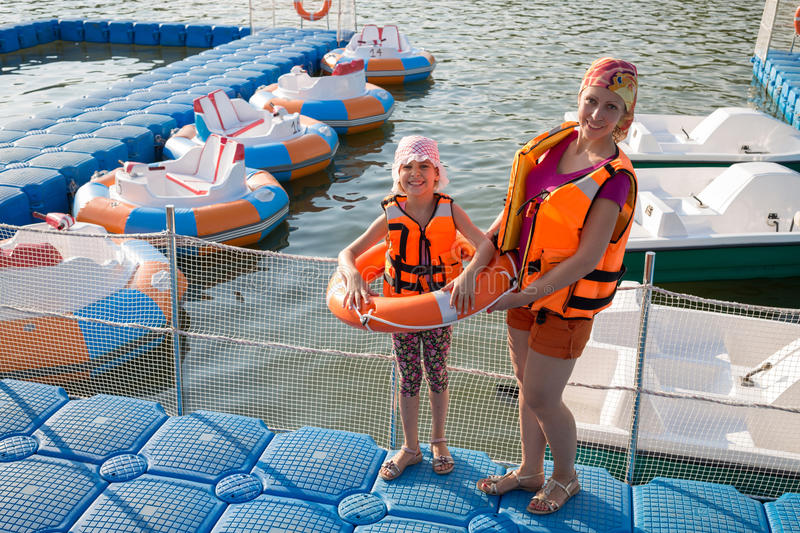 Mother and daughter on the dock with inflatable boats. Mother and daughter on the dock with round inflatable boats with electric motor royalty free stock photography