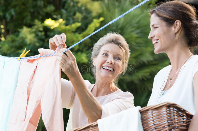 Mother daughter doing laundry royalty free stock photo