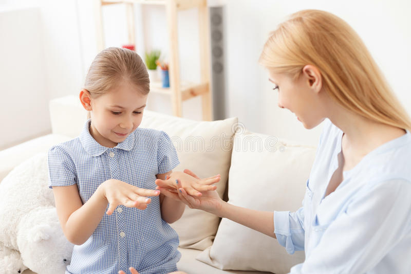 Mother and daughter doing manicure stock photography