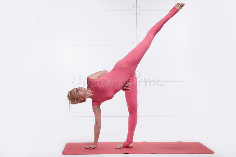 Beautiful blonde engaged in yoga relaxes and meditation royalty free stock images
