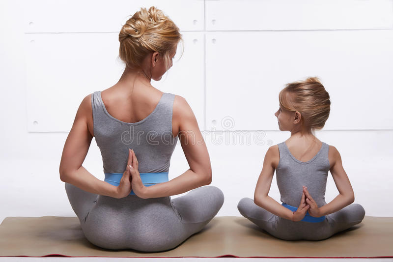 Mother and daughter doing yoga exercise, fitness, gym wearing the same comfortable tracksuits, family sports, sports paired siting. Mother and daughter doing royalty free stock images