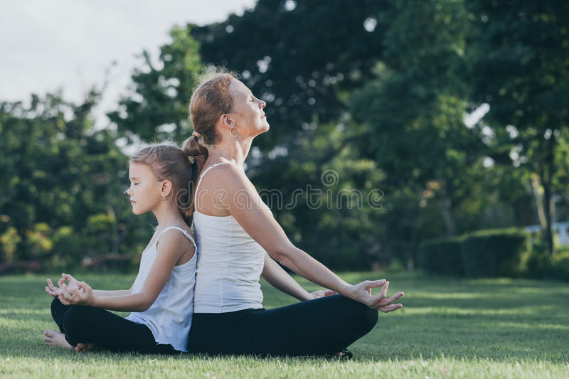 Mother and daughter doing yoga exercises on grass in the park at stock image