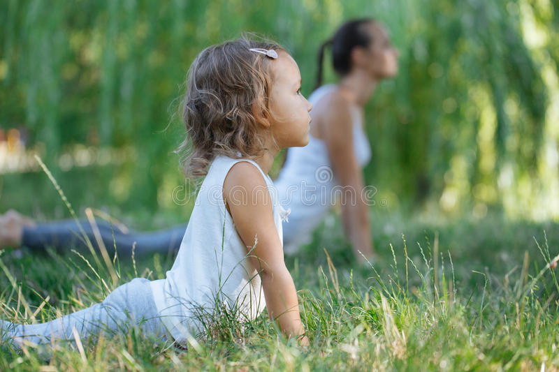 Mother and daughter doing yoga exercises on grass in the park at the day time. royalty free stock images