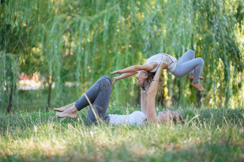 Mother and daughter doing yoga exercises on grass in the park at the day time. stock photography