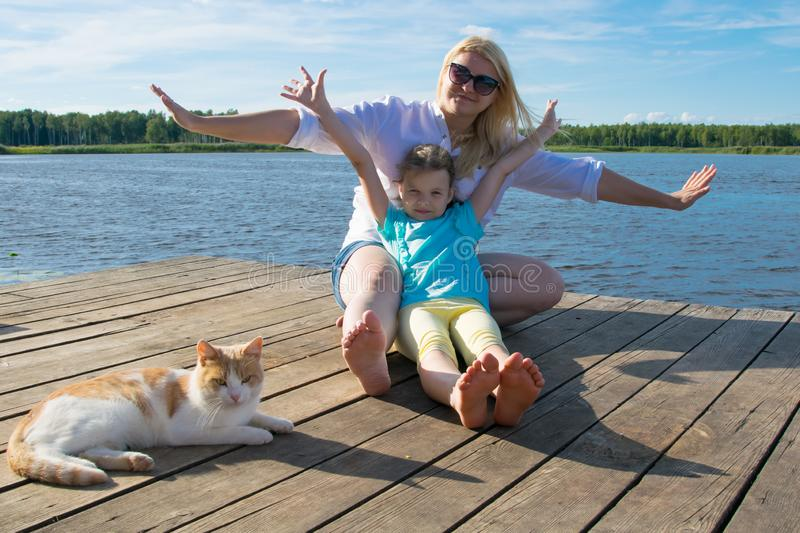 Mother and daughter and a domestic cat, resting on the pier, outdoors, by the lake royalty free stock images