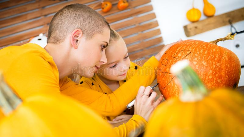 Mother and daughter drawing smiley face on a large Halloween pumpkin. Family decorating pumpkin. stock photos