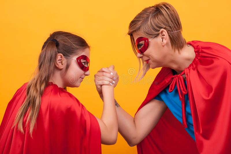 Mother and daughter dressed like superheroes playing arm wrestling over yellow background. stock image