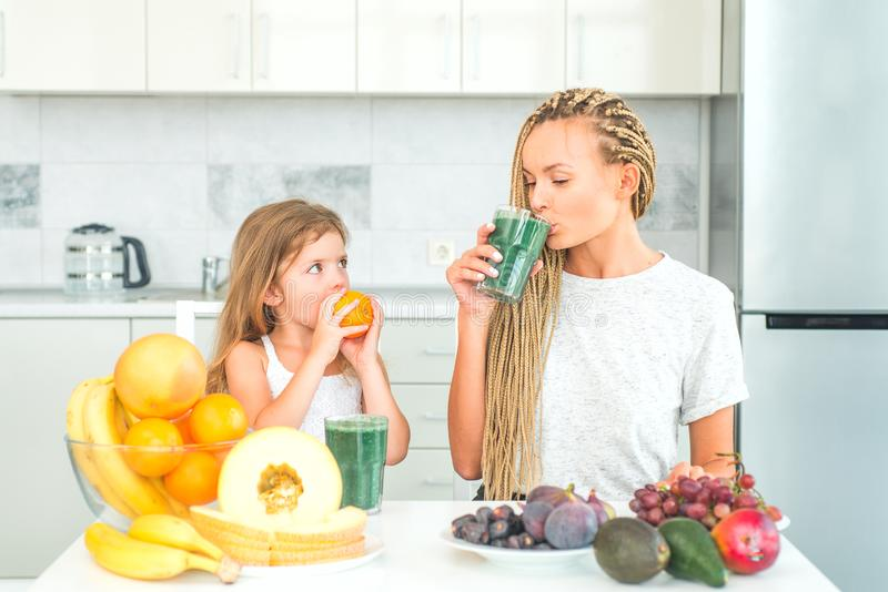 Mother and daughter drinking matcha from glass at home. Food supplements. and spirulina. Mother with her little daughter stock photography