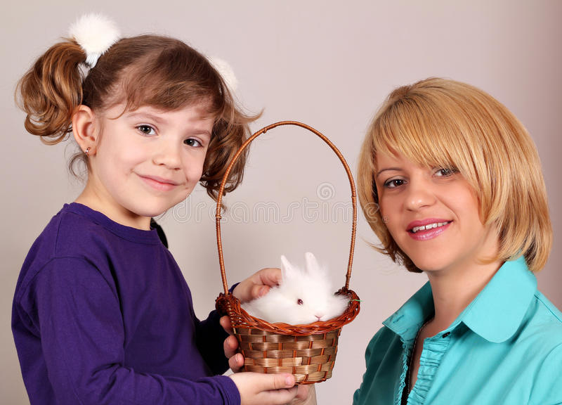 Mother and daughter with dwarf rabbit. Mother and daughter with cute dwarf rabbit royalty free stock photo