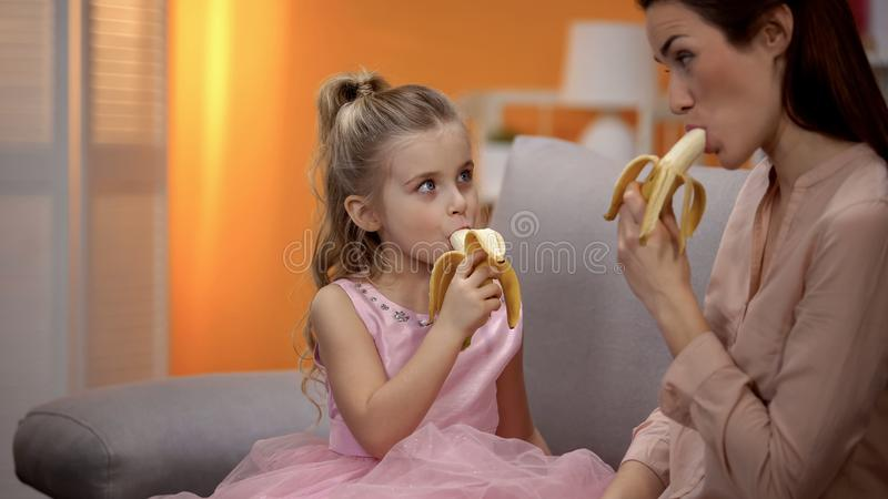 Mother and daughter eating bananas, healthy lifestyle, organic nutrition, diet stock photo