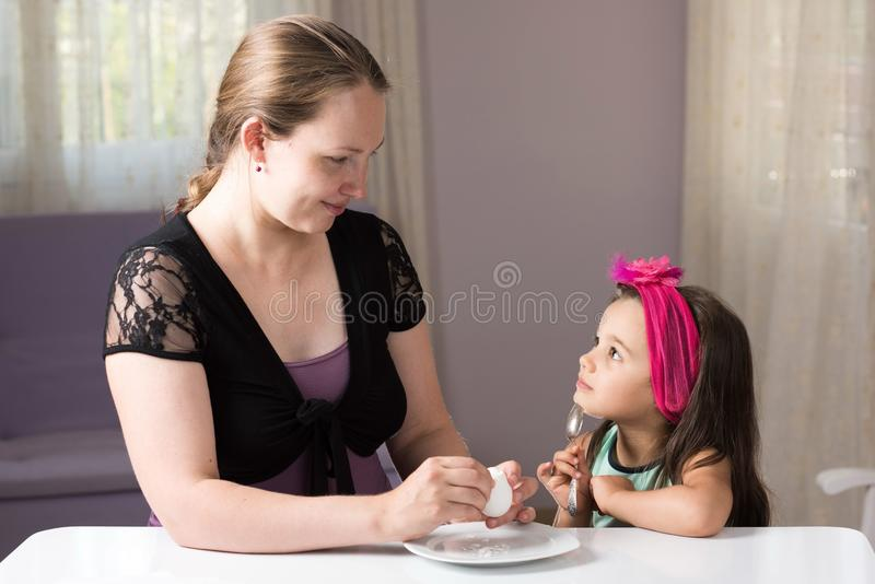 Mother and Daughter Eating Egg royalty free stock photos