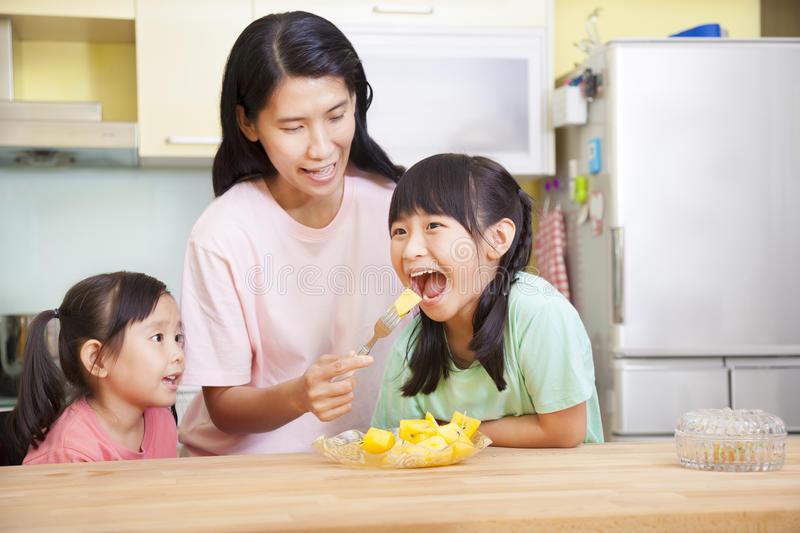 Mother and daughter eating fruits stock photography
