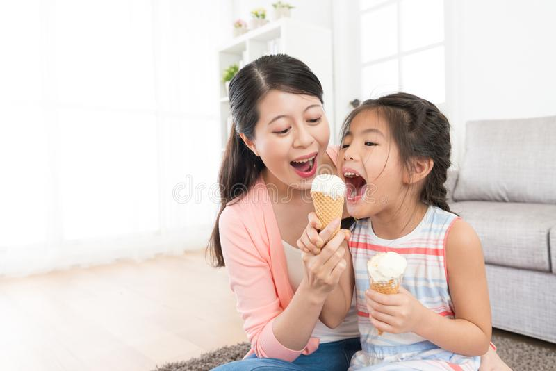 Mother with daughter eating ice cream together royalty free stock image