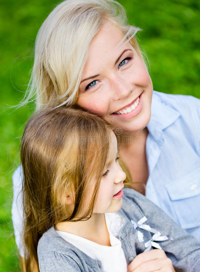 Download Mother And Daughter Embrace Each Other On The Grass Stock Image - Image: 38841999
