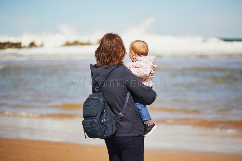 Mother and daughter enjoying Atlantic ocean on the beach stock photo