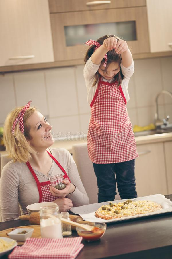 Mother and daughter making pizza stock image