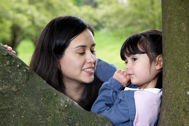 Mother and Daughter Enjoying the Peacefulness of Nature. Mother Looking Lovingly at her Daughter Deep In Thought as she Rest on a Tree stock image