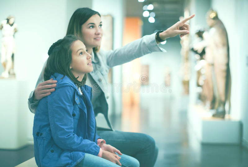 Mother and daughter exploring antique statues stock photo