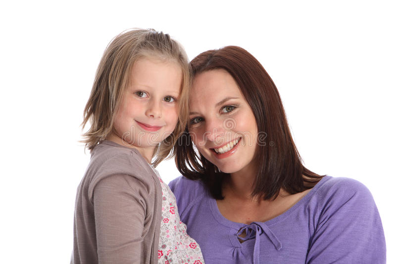 Mother and daughter family portrait happy smiles. Family portrait of mother and daughter, both posing against a white backdrop with big happy smiles. Mum has royalty free stock images