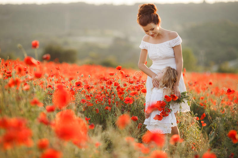 Mother and daughter in a field of blooming poppies. A beautiful young women ,a brunette,with her small daughter,a girl with long wavy,blond hair,both dressed in royalty free stock photography