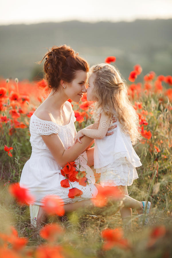 Mother and daughter in a field of blooming poppies. A beautiful young women ,a brunette,with her small daughter,a girl with long wavy,blond hair,both dressed in royalty free stock photo