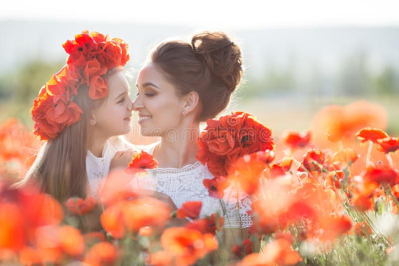 Beautiful mother and her daughter playing in spring flower field royalty free stock images