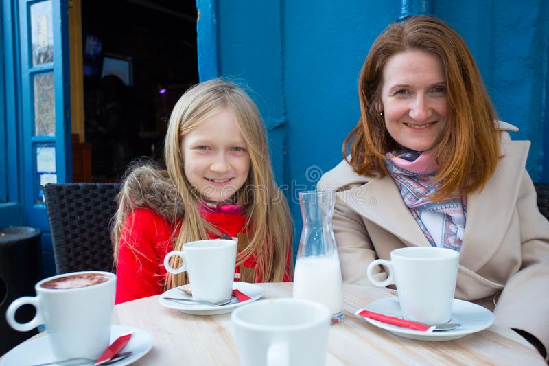 Mother and daughter at the french caffee stock images