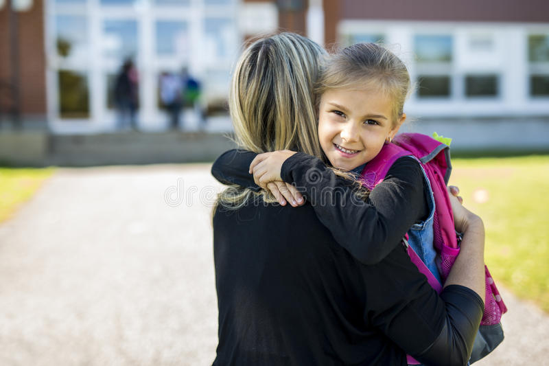 Mother And Daughter in front of a school stock images