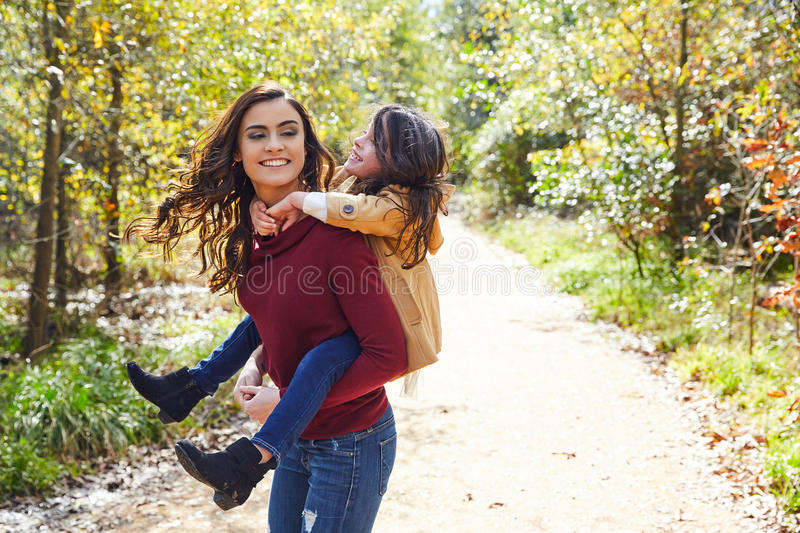 Mother and daughter fun piggyback in a park stock photography