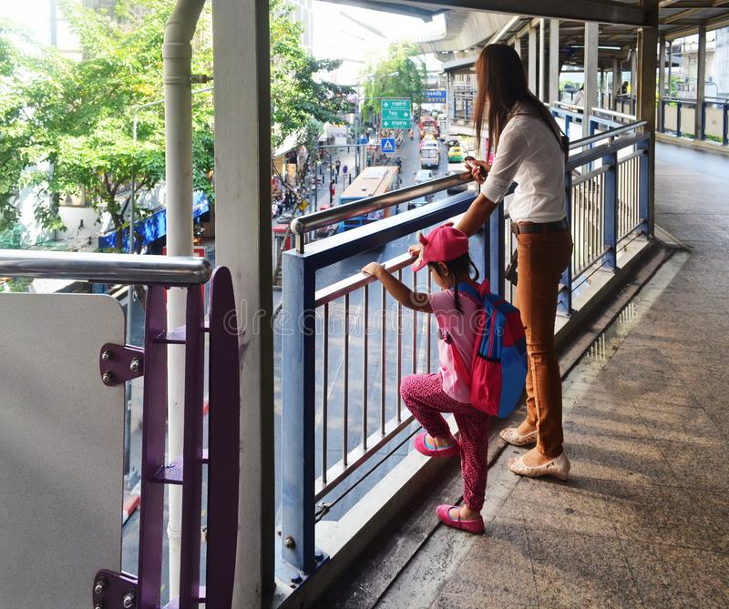 Mother and daughter gaze from an elevated walkway at the street below. royalty free stock photos