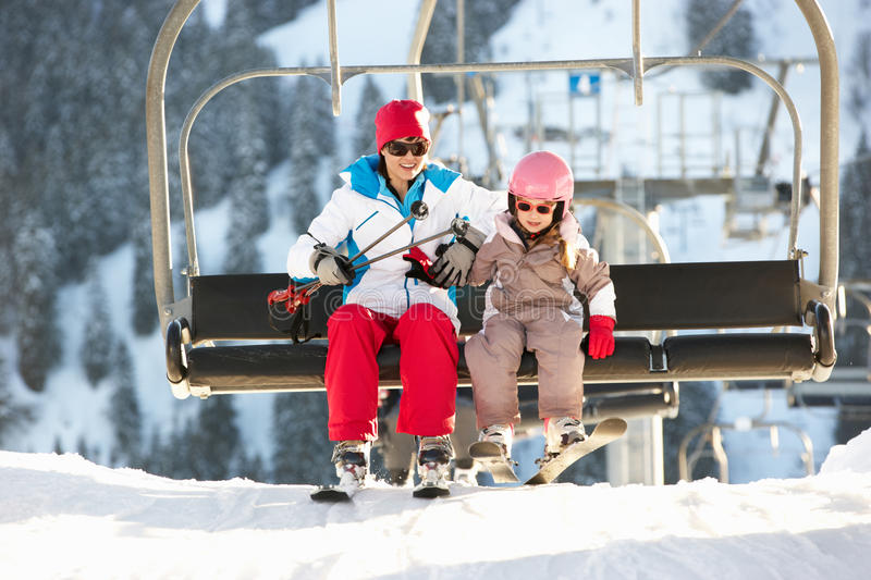 Mother And Daughter Getting Off Chair Lift In Mou. Mother And Daughter Getting Off Chair Lift On Ski Holiday In Mountains royalty free stock photos