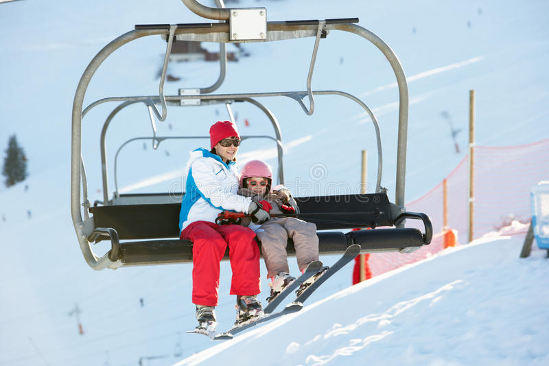 Mother And Daughter Getting Off Chair Lift In Mou. Mother And Daughter Getting Off Chair Lift On Ski Holiday In Mountains stock photography