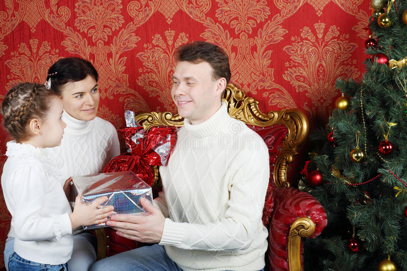 Mother and daughter give gifts to father near Christmas tree. In red room stock images