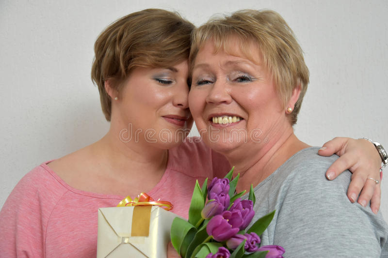 Mother and daughter. Daughter gives flowers and a gift to her mother royalty free stock image