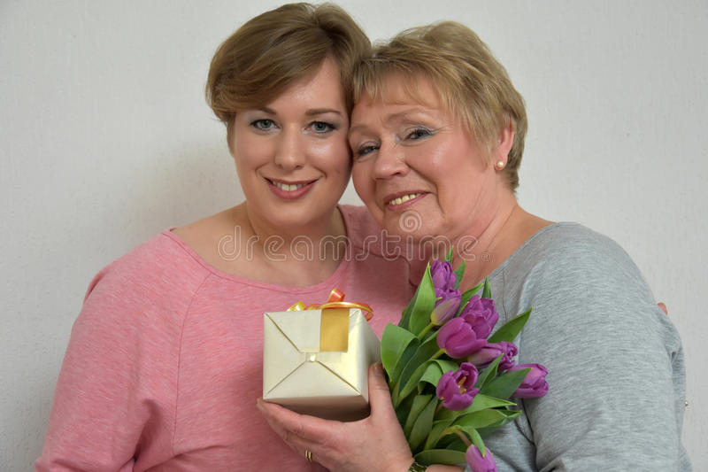 Mother and daughter. Daughter gives flowers and a gift to her mother royalty free stock photo