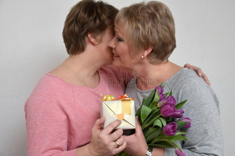 Mother and daughter. Daughter gives flowers and a gift to her mother stock photography