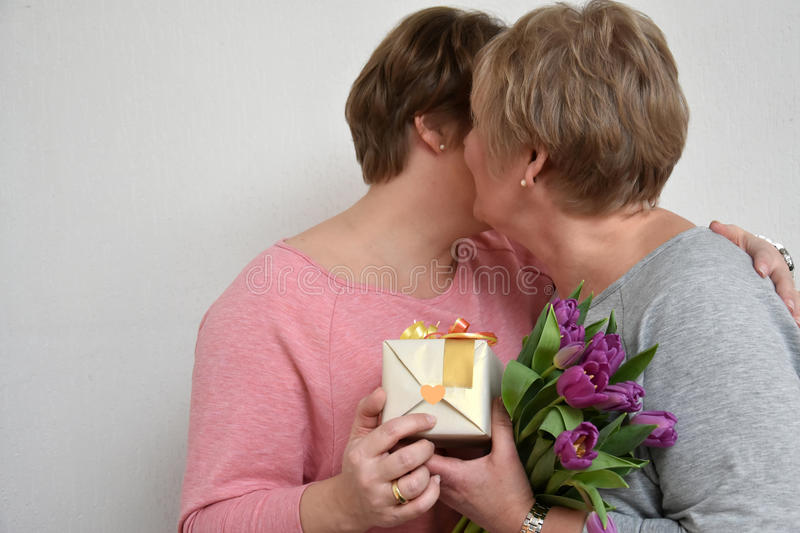 Mother and daughter. Daughter gives flowers and a gift to her mother royalty free stock images
