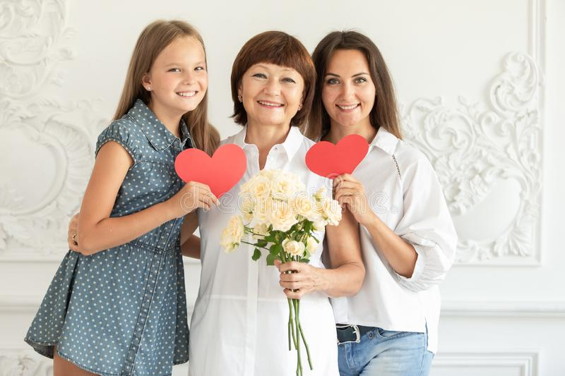 Mother, daughter and granddaughter hug and hold cardboard hearts and a bouquet of flowers royalty free stock image