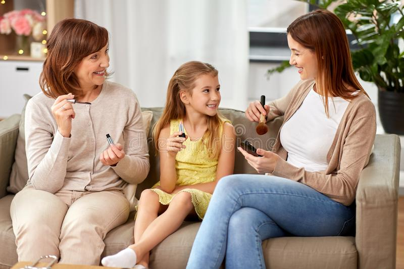 Mother, daughter and grandmother doing make up royalty free stock photos