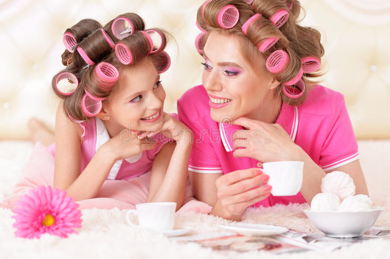 Mother and daughter in hair curlers. Portrait of happy Mother and little daughter in hair curlers with magazine at home stock image