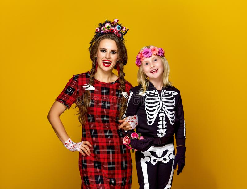 Mother and daughter in halloween costume on yellow royalty free stock photography